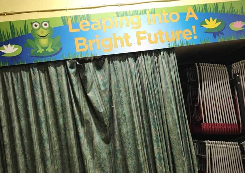 The stage area in the main hall of the school was transformed with a display featuring the school motto.