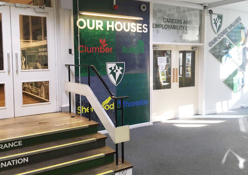 A transformed reception area featuring core values displays, house boards and directional signage.
